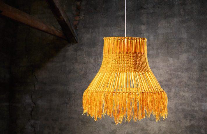 Senapsgul lampa gjord av mattrester mot grå bakgrund
