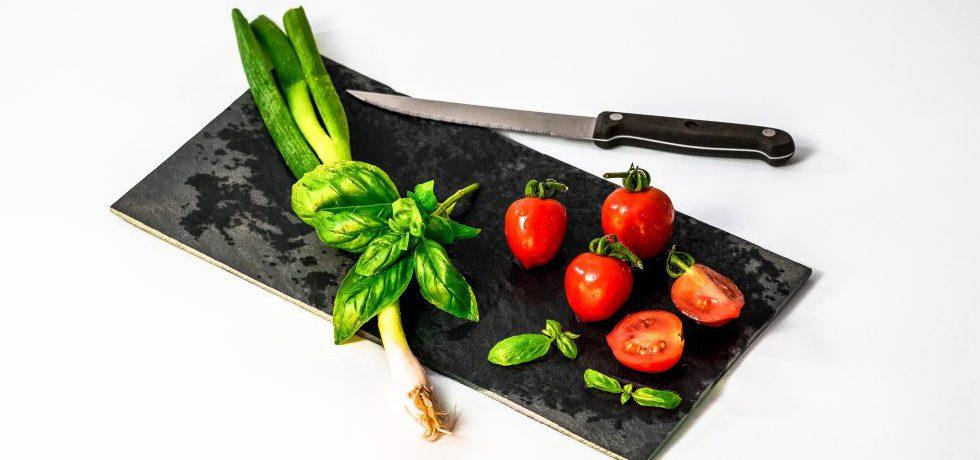 Basilika och tomater på en rektangulär svart bräda, en kniv ligger ovanför.