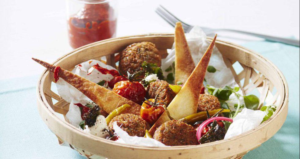 Maträtt med falafel i en korg på bord med vit du och mintgrön bordstablett.