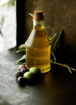 Olja i glasflaska på mörkt bord, frukter ligger bredvid