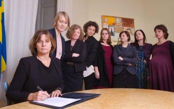 Åtta kvinnor samlade när Isabella längst fram sittandes undertecknar papper, de andra stående bakom.