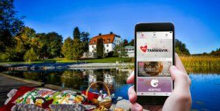 Smartphone med Karmaappen öppen, i bakgrunden en sjö och ett vitt större hus, en konferensanläggning
