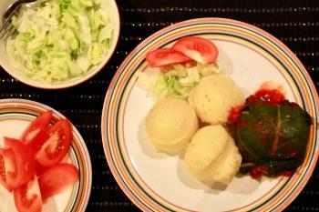 En tallrik med tre kulor potatismos, en mangolddolm och lite sallad och tomat. Till vänster fat med klyftade tomater och en skål med grönsallad.