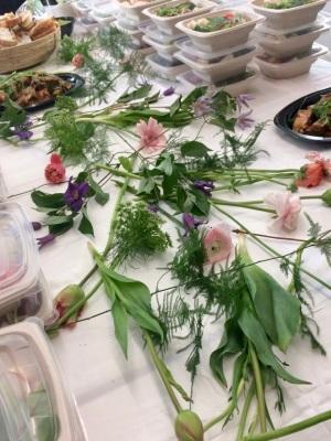 Bord med färska blommor lagda på vit duk, i bakgrunden skymtar sallad i portionslådor