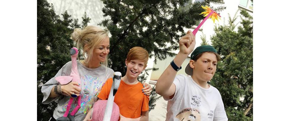 En blond kvinna med två pojkar till höger, en rödblond med orange tshirt och en med bakåtvänd keps och vit tshirt