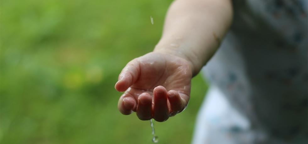 En hand hålls fram för att fånga vattendroppar