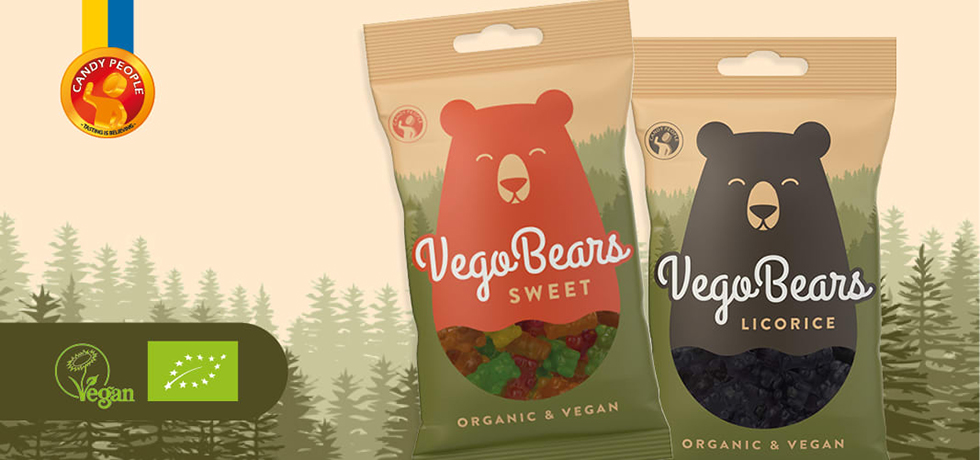 Två godispåsar med illustrerade björnar på, en roströd och en svart. Tillvänster veganmärkning