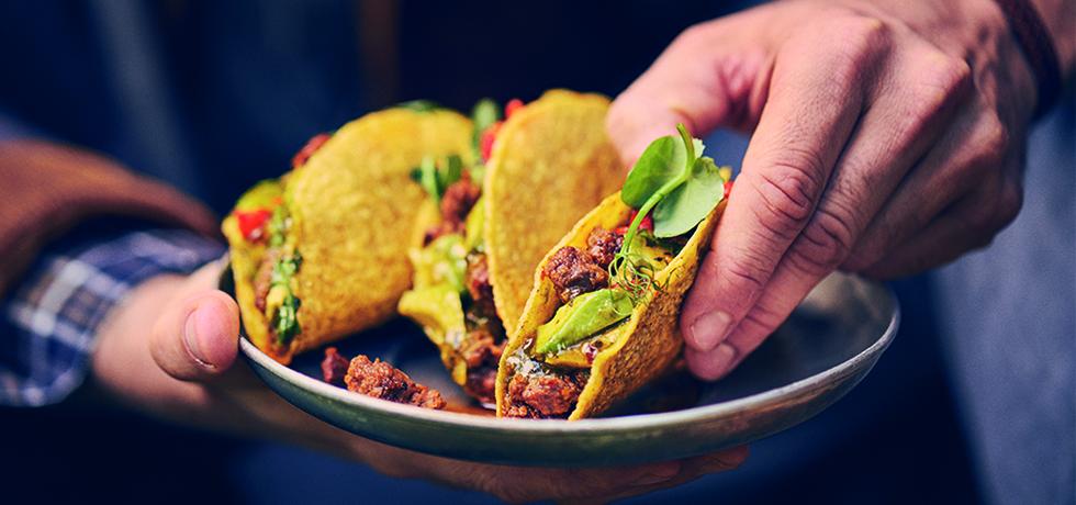 Tre stycken taco bredvid varandra, till höger en hand som ska ta en taco