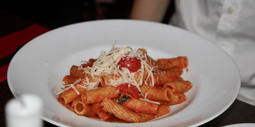 Vid, djup tallrik med penne i tomatsås, riven ost ovanpå